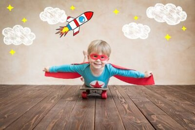 Fototapete Portrait of super hero on the skateboard. Happy child playing at home. Superhero kid having fun. Success, creative and start up concept