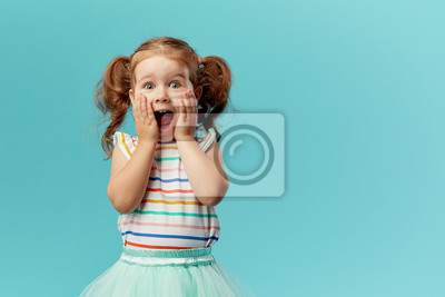 Fototapete Portrait of surprised cute little toddler girl child standing isolated over blue background. Looking at camera. hands near open mouth