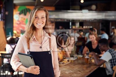 Fototapete Portrait Of Waitress Holding Menus Serving In Busy Bar Restaurant