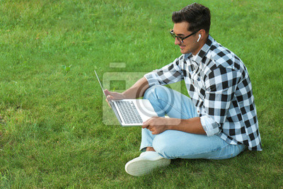 Fototapete Portrait of young man with laptop outdoors