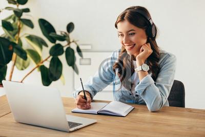 Fototapete portrait of young smiling woman in headphones taking part in webinar in office