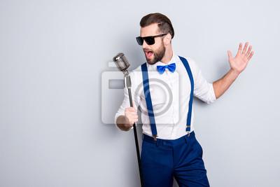 Fototapete Porträt des hübschen attraktiven Sängers in den blauen Hosen mit Hosenträgern und schwarzen Gläsern, Gesangschlag mit offenem Mund in der Mikrofongeste mit der Hand lokalisiert auf grauem Hintergrund
