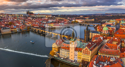 Fototapete Prague, Czech Republic - Aerial panoramic drone view of the world famous Charles Bridge (Karluv most) and St. Francis Of Assisi Church with a beautiful winter sunset. St. Vitus Cathedral at background