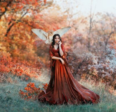 Fototapete pretty young girl with black hair in cold forest, orange foliage of trees, fairy of autumn season in long red burgundy vintage dress with chic train, lady with white owl on shoulder, bloody sorceress