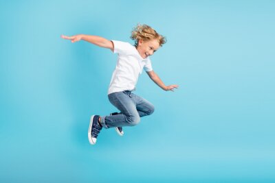 Fototapete Profile photo of young boy jump fly movement hands wear white shirt jeans sneakers isolated blue color background