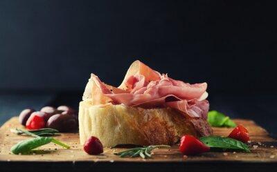 Fototapete Prosciutto mit Brot auf einem Holzbrett mit Oliven