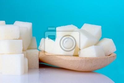 raffiniertem Zucker in hölzernen Löffel auf blauem Hintergrund