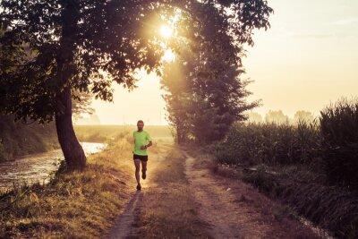 Fototapete Ragazzo che corre all'alba su strada di campagna in estate