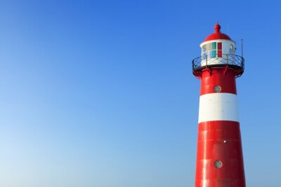 Fototapete Red and white lighthouse and a clear blue sky