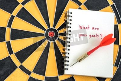 Red dart target arrow on open notebook with alphabet letters hand writing word what are you goal and question mask over dartboard background, Marketing concept