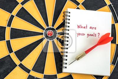 Red Dart Ziel Pfeil auf offene Notebook mit Alphabet Buchstaben Hand schreiben Wort was sind Sie Ziel und Frage Maske über Dartboard Hintergrund Marketing-Konzept