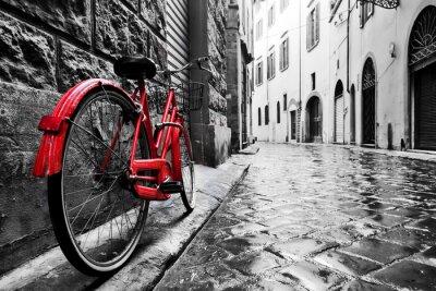 Fototapete Retro Vintages rotes Fahrrad auf Kopfsteinstraße in der alten Stadt. Farbe in schwarz und weiß