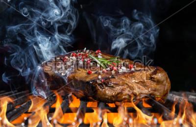 Fototapete Rindfleischsteak auf Grill im Feuer mit schwarzem Hintergrund