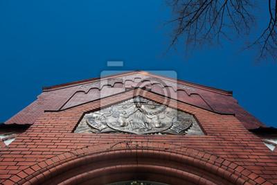 Rote Backsteinfassade der katholischen Kirche gegen den blauen Himmel
