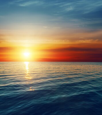 Fototapete roter Sonnenuntergang über dunklen Wasser