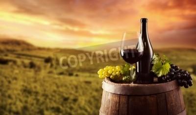 Fototapete Rotweinflasche und Glas auf hölzernem Faß. Weinberg auf Hintergrund