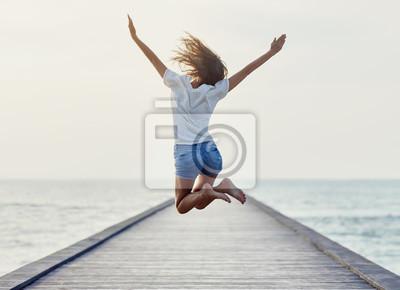 Fototapete Rückansicht des springenden Mädchens auf dem Pier