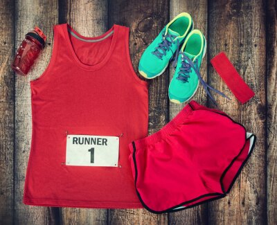 Fototapete Running gear laid out ready for race day, rustic wooden background