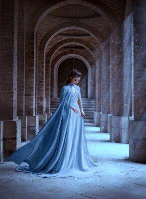 Fototapete Sad Snow Queen walks in old castle. blue silk long raincoat train flying motion. Elven hairstyle cute face. Vintage fantasy art retro style. Frozen Fabulous woman photo shoot. sun magic shine rays