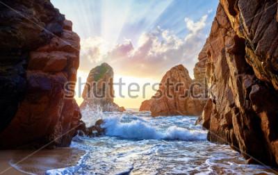 Fototapete Sandstrand zwischen Felsen am Abendsonnenuntergang. Ursa Beach in der Nähe von Cape Roca (Cabo da Roca) an der Atlantikküste in Portugal. Sommerlandschaft