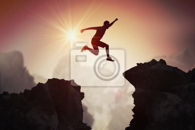 Fototapete Schattenbild des jungen Mannes springend über Berge und Klippen bei Sonnenuntergang.