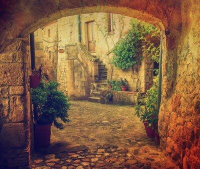 Fototapete Schmale Straße der mittelalterlichen Tuff-Stadt Sorano mit Bogen, grüne Pflanzen und Kopfsteinpflaster, Reisen Italien Jahrgang Hintergrund