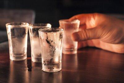 Fototapete Schnapsglas Wodka in der Hand auf einem Holztisch.