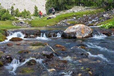 Fototapete Schnelle und breite Kaskade Fluss schnell bewegende Wasser lebendige Felssteinen und Gruppe von Menschen zu Fuß auf der grünen Wiese im Hintergrund