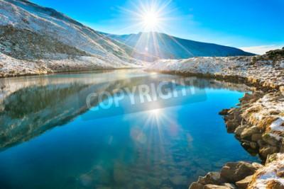 Fototapete Schöne blaue See in den Bergen, Morgen Sonnenaufgang Zeit. Landschaft mit schneeglänzenden sonne