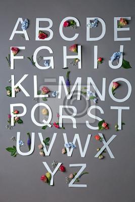 Schöne Blumenzusammensetzung mit den Buchstaben gemacht vom Papier auf grauem Hintergrund