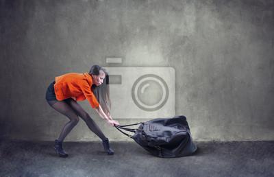 Schöne Frau, die schwere Tasche mit einigen Schwierigkeiten