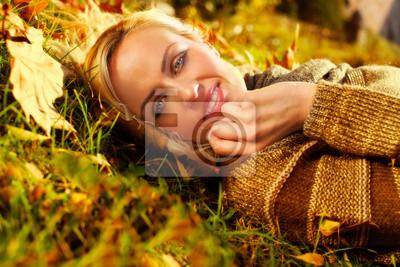 schöne Frau liegend auf Herbstlaub