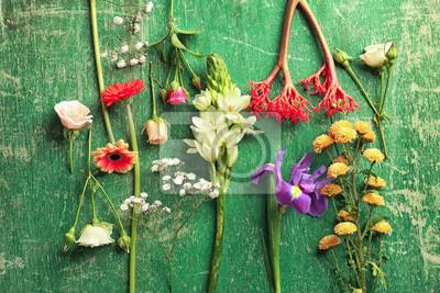 Schöne frische Blumen auf grünem Holzuntergrund