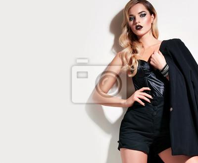 Fototapete Schönes junges Mädchen mit dem blonden Haar in der modernen  schwarzen Kleidung - eine lange c92ce1f179