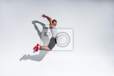 Fototapete Seitenansicht des jungen Afroamerikanersportlers, der auf Grau springt