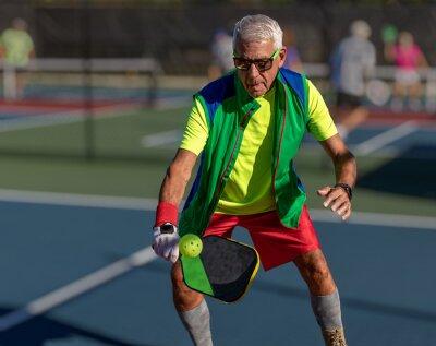 Fototapete Senior man hitting a pickleball with paddle