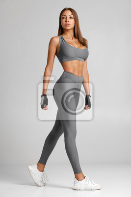Fototapete Sexy fitness woman. Beautiful athletic girl on the gray background