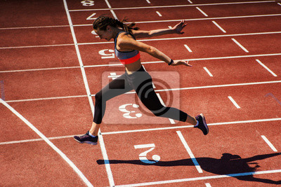 Fototapete Side view of female teen athlete in sports bra and tights successfully finishing race on track at stadium