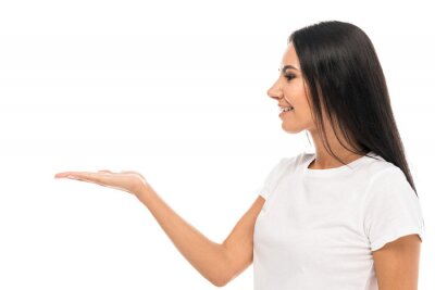 Fototapete side view of happy woman pointing with hand isolated on white