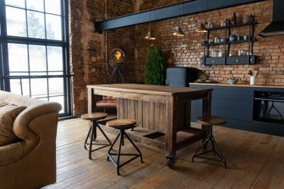 Fototapete Side view on a wooden table and spacious industrial loft kitchen with vintage decor and black cabinets