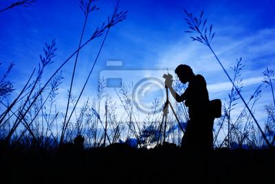 Silhouette des Fotografen auf einem Gras auf einem Vordergrund