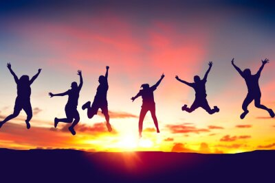 Fototapete Silhouette happy friends jump on sunset sky at top of mountain abstract background.