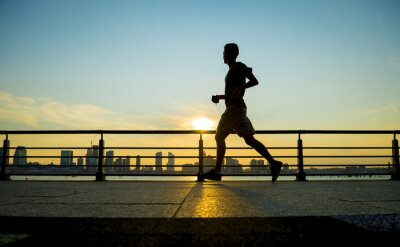 Fototapete Silhouette Jogger laufen bei Sonnenuntergang vor der Skyline der Stadt
