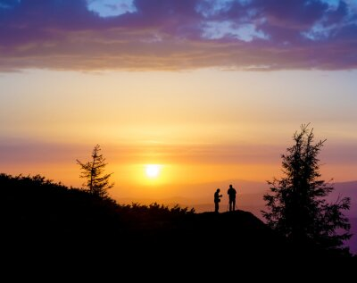 Fototapete Silhouetten von zwei Menschen, die auf einem Felsen in der Nähe des Baumes und auf der Suche nach der Sonne. Sonnenuntergang in den Bergen. Sommer in den ukrainischen Karpaten