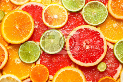 Fototapete Slices of fresh citrus fruits as background, top view