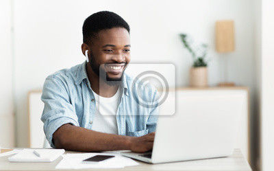 Fototapete Smiling african-american guy in earphones studying foreign language online