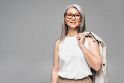 Fototapete smiling asian businesswoman in eyeglasses isolated on grey