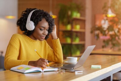 Fototapete Smiling black girl with headset studying online, using laptop