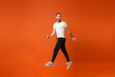 Fototapete Smiling funny young man in casual white t-shirt posing isolated on bright orange wall background studio portrait. People lifestyle concept. Mock up copy space. Having fun, fooling around, jumping.