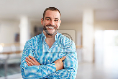 Fototapete Smiling man standing in business center